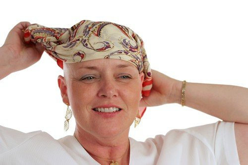 A beautiful woman, bald from chemotherapy,  prepares to remove the scarf covering her head.